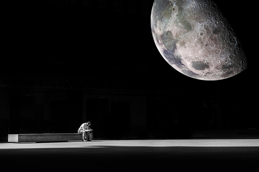 Lone person sitting in empty place under a huge moon